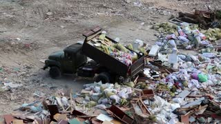 Dump truck in the city dump. Car unloads garbage in a landfill. Dump truck unloads material debris on junkyard