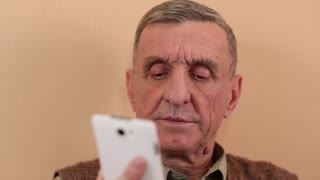 Elderly man with smartphone. Senior man with white smartphone speaks and smiles. Aged man talks on the cell phone