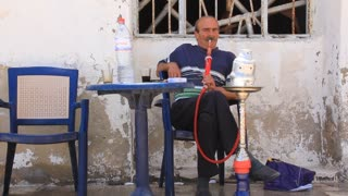 Elderly person smoking hookah in Sousse, Tunisia