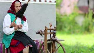 Elderly woman sits on bench and works with distaff with spinning wheel. Ukrainian old woman sits on bench near his house and spin yarn. Female with spinning wheel, handicraft