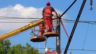 Electrical technicians repair high-voltage line. Workers in uniform