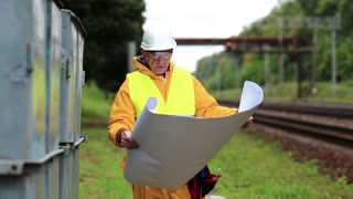 Electrician in yellow uniform with installation diagram in hands. Railway worker in yellow uniform with design drawings in hands. Railway worker in white hard hat with wiring scheme in hands