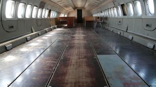 Empty interior of old airliner. Inside the airplane. Interior of aircraft without passenger seats