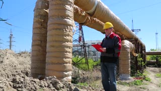 Engineering supervision. Service engineer at heat electropower station. Worker in yellow hard hat near heating main pipeline
