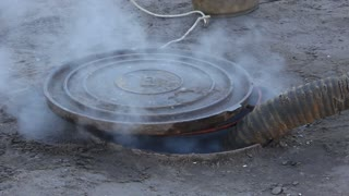 Exhaust of water from heat chamber. Sewer manhole