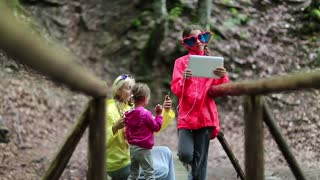 Family with electronic devices on the wooden bridge in the forest. Women in color jackets with tablet pc and smartphone. Mother and two daughters with smartphone and tablet computer on the nature