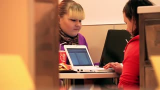Fast-food and obesity. Two girls with laptop eat and drink in fast food restaurant