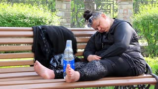 Fat woman sleep on a bench
