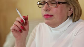 Female smoker. Senior woman with glasses smoking a cigarette, close up shot