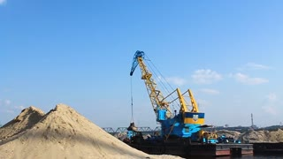 Floating crane on the river unloading sand