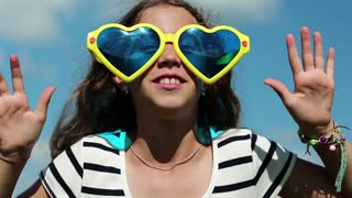 Funny girl in big glasses in shape of hearts looks at the camera and makes faces. Merry girl in sunglasses looks at the camera and grimaces