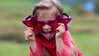 Funny girl in big glasses in shape of stars looks at camera and makes grimaces. Beautiful little girl in pink glasses looks at the camera