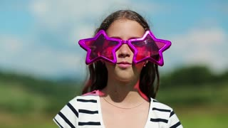 Funny girl in big glasses in shape of stars looks at the camera and makes faces. Merry girl in sunglasses looks at the camera and grimaces