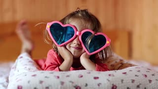 Funny girl in big glasses in the shape of hearts lies on the bed. Little girl lies on the pillow looks at the camera and shows his tongue