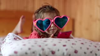 Funny girl in big glasses in the shape of hearts with smartphone lies on the bed. Little girl lies on the pillow, holds in hands red mobile phone. Funny bambino with cell phone