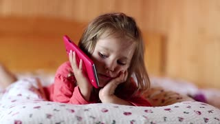 Funny girl with smartphone lies on the bed. Little girl lies on the pillow, holds in hands red mobile phone and gesticulate