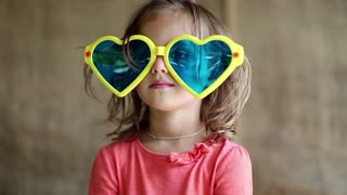 Funny little girl in big glasses looks at camera, shows his hands and tongue. Little girl in big sunglasses in the shape of hearts looks at the camera