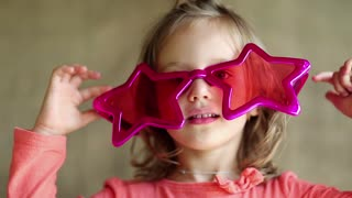Funny little girl in big pink glasses in the shape of stars looks at the camera. Pretty little girl in pink glasses looks at the camera. Girl with glasses