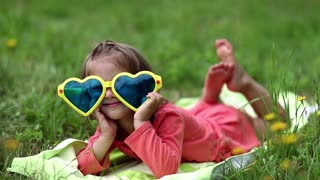 Funny little girl in big sunglasses in the shape of hearts lies on green grass and makes grimases. Beautiful little girl in glasses lies on the green grass and looks at the camera