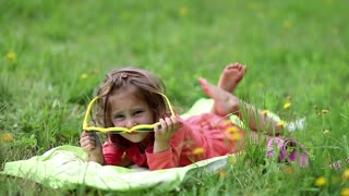 Funny little girl in big sunglasses in the shape of hearts lies on green grass. Beautiful little girl in glasses lies on the green grass and looks at the camera