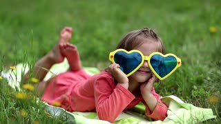 Funny little girl in big sunglasses in the shape of hearts lies on green grass. Funny girl show his tongue. Beautiful little girl in glasses lies on the green grass and looks at the camera