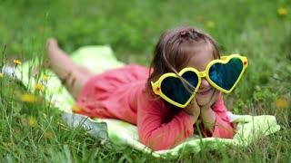 Funny little girl in big sunglasses in the shape of hearts lies on the grass. Beautiful little girl in glasses lies on the green grass and looks at the camera. Funny girl show his tongue