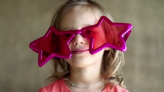 Funny little girl in pink glasses looks at the camera. Pretty little girl in big glasses in the shape of stars looks at the camera