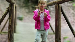 Funny little girl in pink jacket on the nature. Little girl stands on a wooden bridge and does dance moves