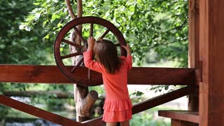 Funny little girl in red dress turn wooden wheel. Little girls turn wooden wheel