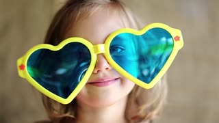 Funny little girl in yellow and blue glasses looks at the camera and shows tongue. Little girl in big sunglasses in the shape of hearts looks at the camera, close up shot
