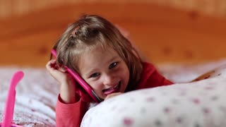 Funny little girl lies on the pillow and holds in hands red mobile phone. Little girl with smartphone lies on the bed and shows his tongue