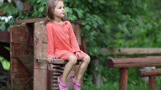 Funny little girl sits on the chair with spring. Little girl in red dress sits on a bench