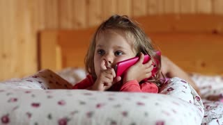 Funny little girl with red smartphone lies on the bed and picks his nose. Little girl lies on the pillow and holds in hands mobile phone. Little girl with red cell phone lies on the sofa