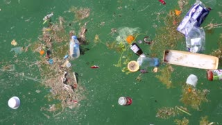 Garbage floats in the sea. Muddy water. Abuse of environment