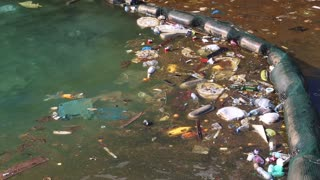 Garbage floats in the sea near the coast. Muddy water. Abuse of environment
