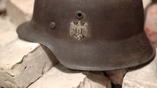 German 20th century WWII nazi helmet lies on ruins of a building. Iron German army helmet of WW2. Nazi army helmet of second world war