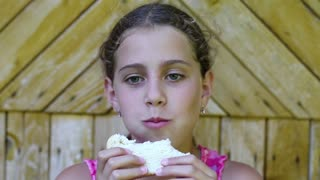 Girl eats bread. Beautiful girl eats slice of bread and smiles