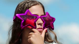 Girl in big pink glasses in the shape of stars looks around and thinks. Beautiful girl in sunglasses on the nature