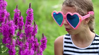 Girl in big sunglasses smells flowers. Beautiful girl in big glasses in the shape of hearts near purple flowers. Flower - Epilobium angustifolium or willowweed, fireweed, sally-bloom, blooming sally