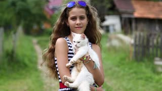 Girl in blue sunglasses holds in hands white cat. Pretty girl holds in hands white cat and looks at the camera. Unique cat has one blue eye and one yellow eye, it is seen in high resolution video