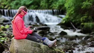 Girl in glasses in shape of hearts with tablet pc sits near small river. Pretty girl playing the game on tablet computer. Girl in red jacket with white tablet pc sits on big stone near river in forest