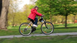 Girl in red jacket on bicycle