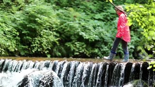 Girl in red jacket walks along small overflow dam on the river in the forest. Girl walks on the brook in the wood