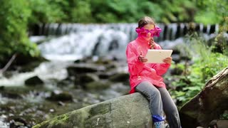 Girl in red jacket with white tablet pc sits on big stone near river in forest. Girl in big glasses in shape of stars with tablet pc sits near brook. Nice girl playing the game on his tablet computer