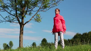 Girl in red sports jacket make physical exercises on the nature near tree. Physical activity helps burn up calories. Girl goes in for sports. Girl engaged in fitness. Morning physical exercises