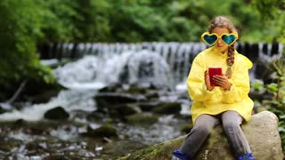 Girl in sunglasses in the shape of hearts with red smartphone sits near small river. Pretty girl playing the game on smartphone. Little girl in yellow jacket with phone sits on big stone near river