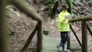 Girl in yellow jacket stands on bridge and uses tablet computer. Pretty girl looks and flips through the photos in his tablet pc. Girl in windcheater with white tablet pc stands on wooden foot bridge