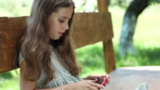 Girl playing the game on his smartphone. Beautiful girl with red smartphone sits on the bench. Nice girl with red cell phone sits on the bench