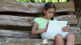Girl playing the game on his tablet computer. Little girl sits on the swing bench and uses Tablet PC. Beautiful girl with tablet PC. Pretty girl with tablet computer sits on swing bench in garden