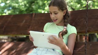 Girl playing the game on his tablet computer. Pretty girl with tablet computer sits on the swing bench. Little girl sits on the swing bench and uses tablet PC
